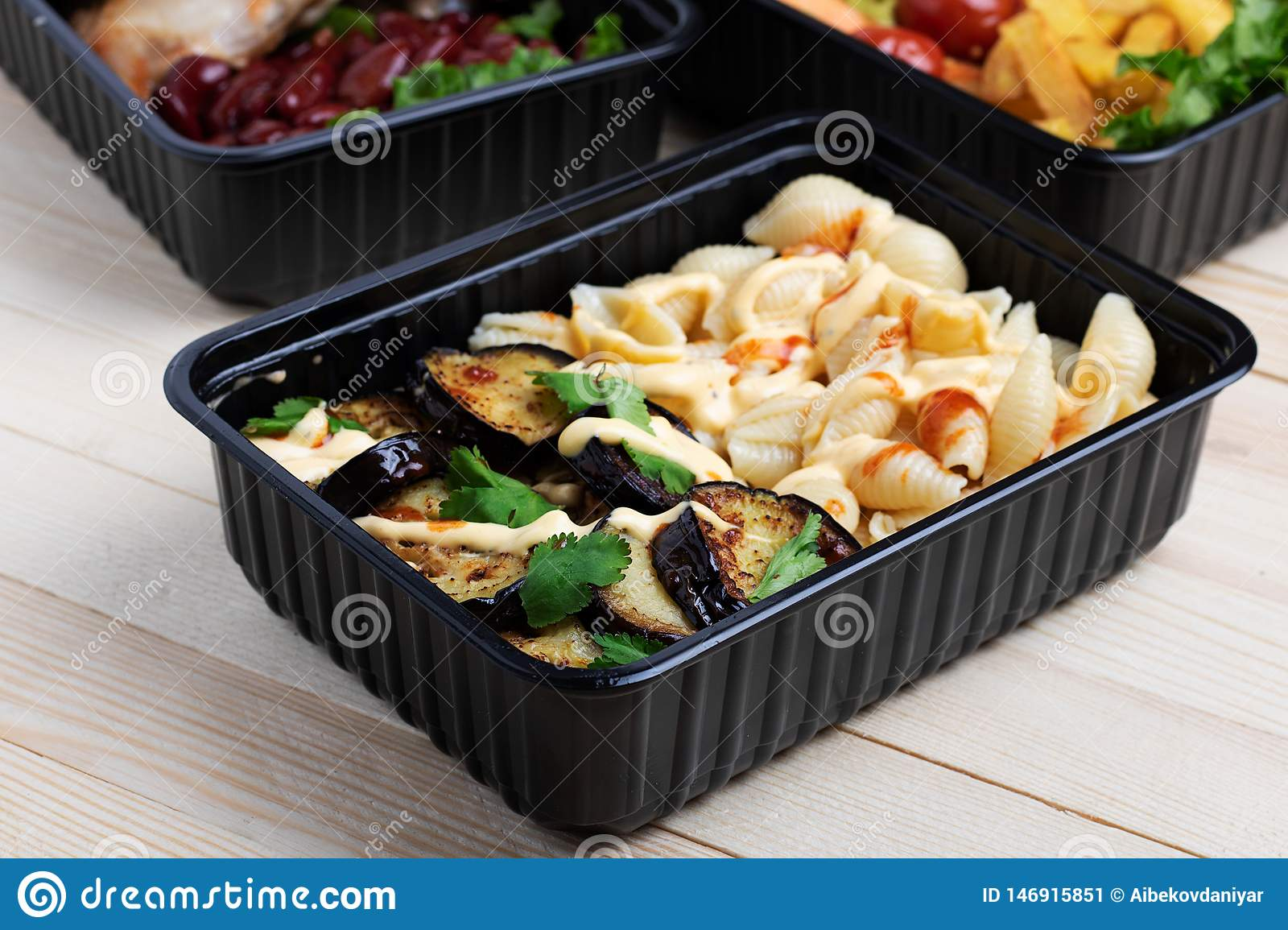 Fried eggplants in container with grilled chicken wings and raw vegetables on rustic background, cherry tomato and micro greenss