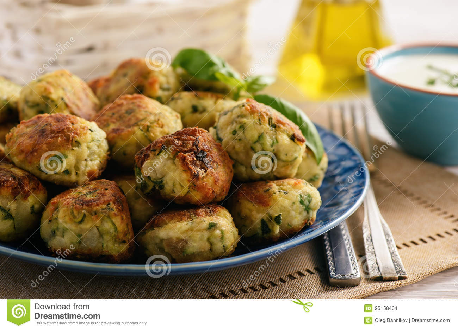 Fried crispy zucchini balls with feta cheese- vegetarian food.