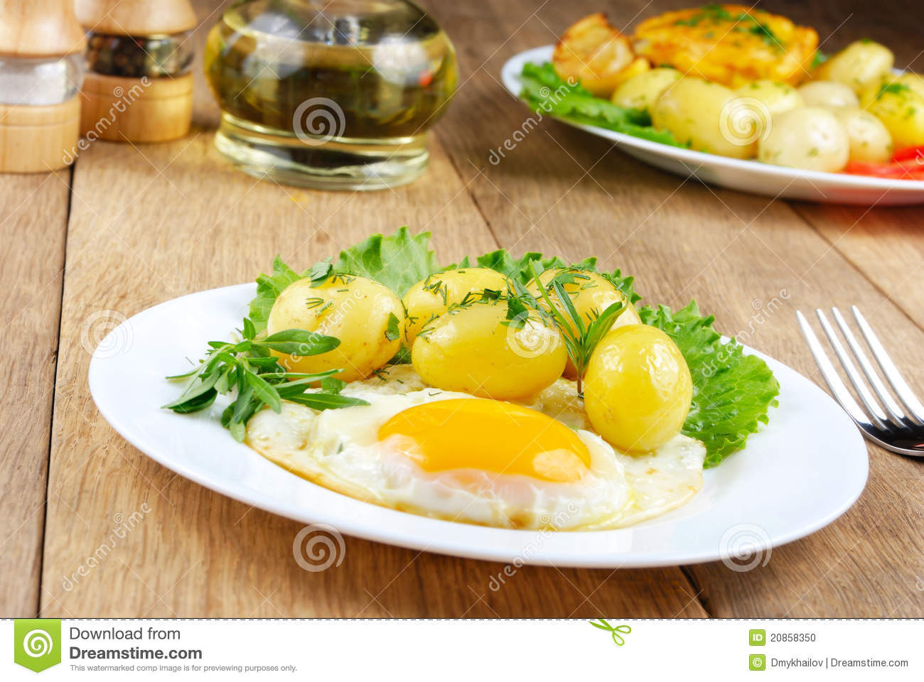 Fried egg with boiled new potatoes, lettuce and herbs in the white ...