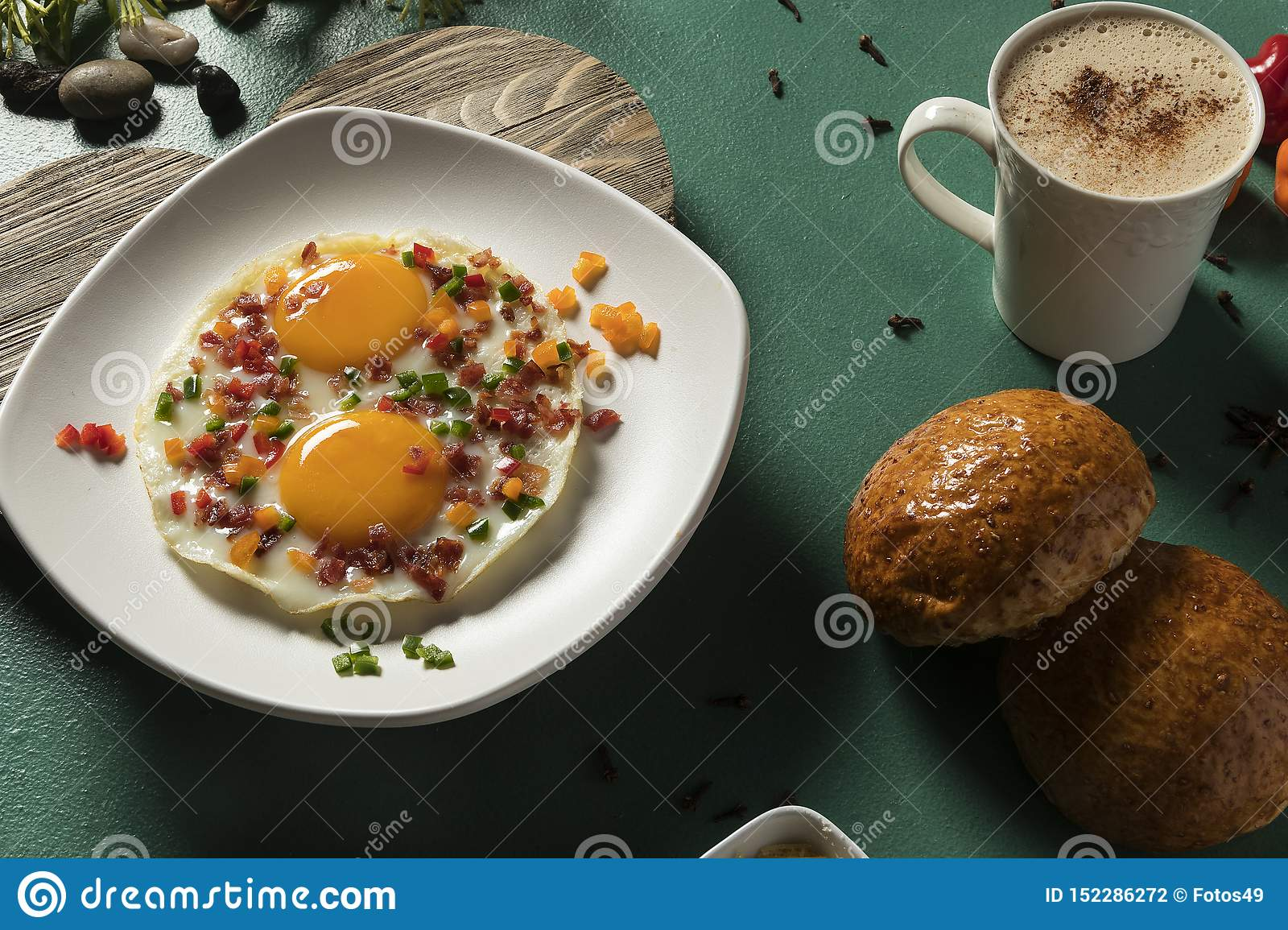Fried eggs with bacon, red cucumber and green bread and chocolate on green background