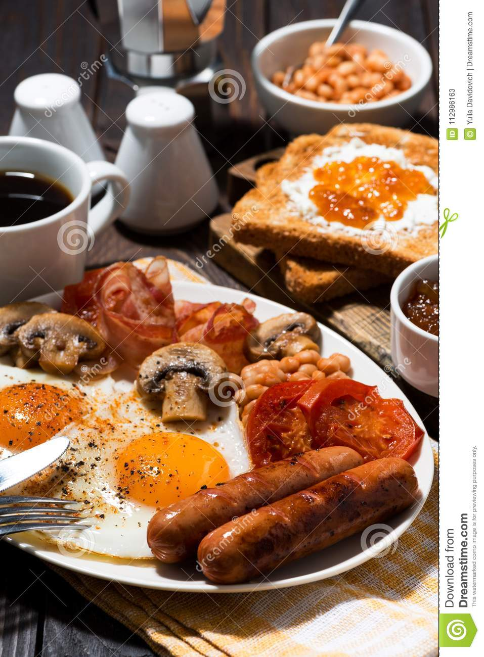Fried eggs with bacon, sausages and vegetables, vertical closeup