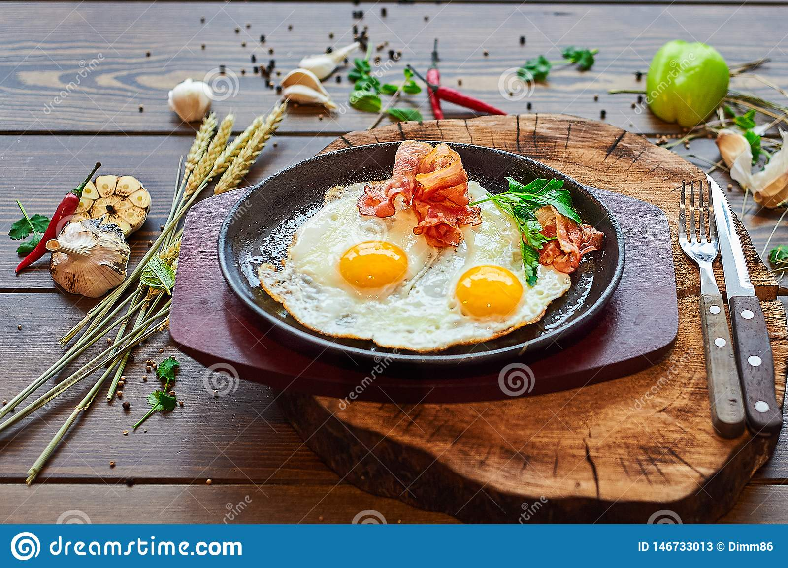 Fried eggs with beacon on a stone plate