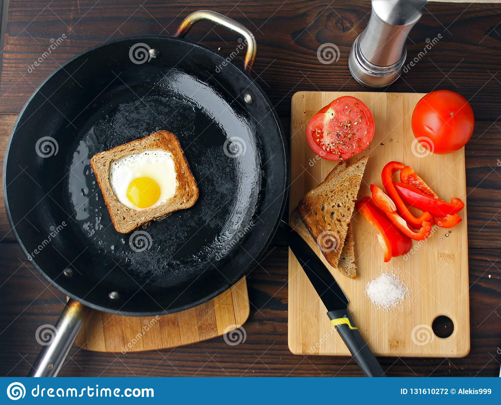 Fried eggs in bread in a pan with cut vegetables on the table.