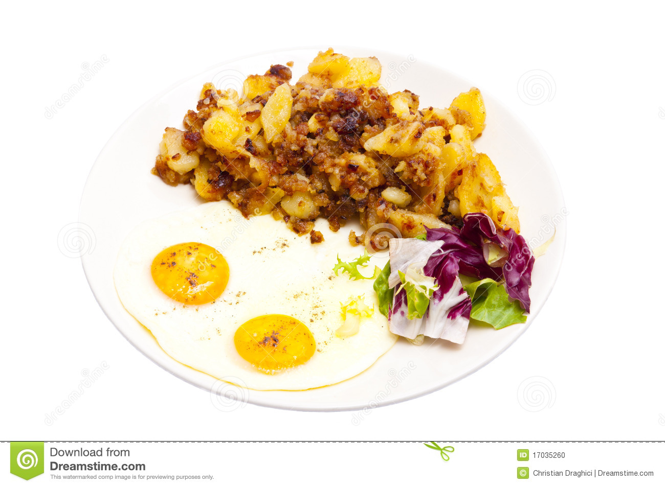 Homemade fried potatoes with eggs sunny side up and vegetables on a ...