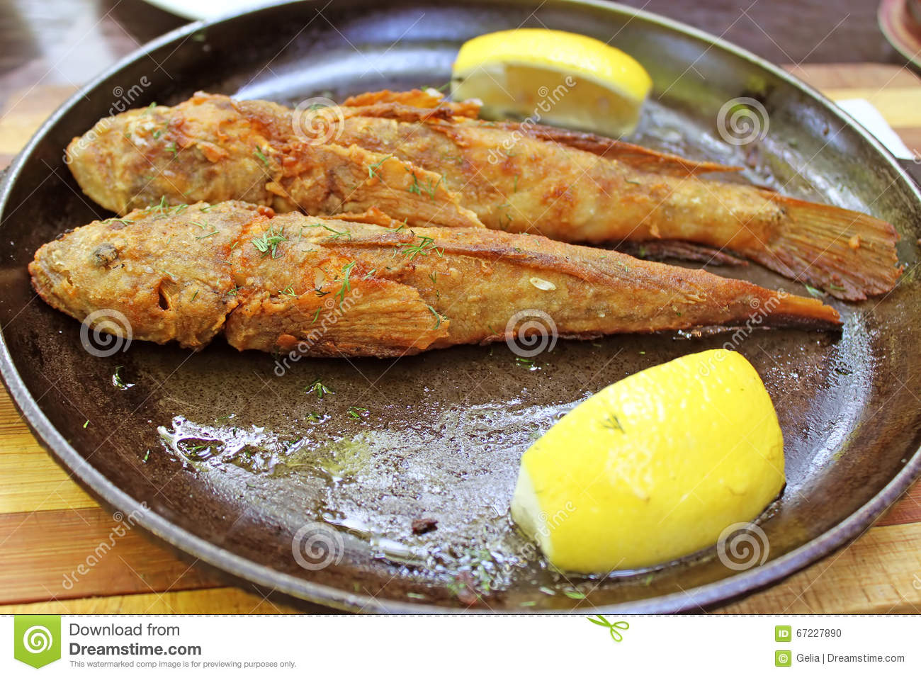 Fried red mullet fish on a wooden plate with lemon and for Eating mullet fish