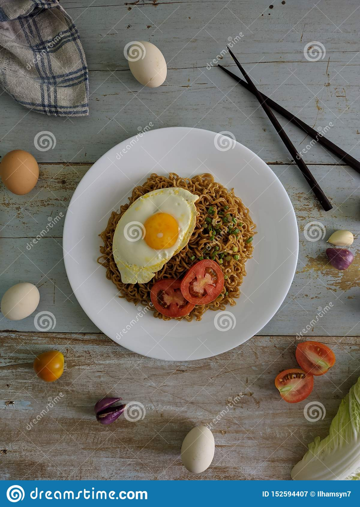 Fried noodles served with fried egg. Food flat lay concept. From top view on wood background