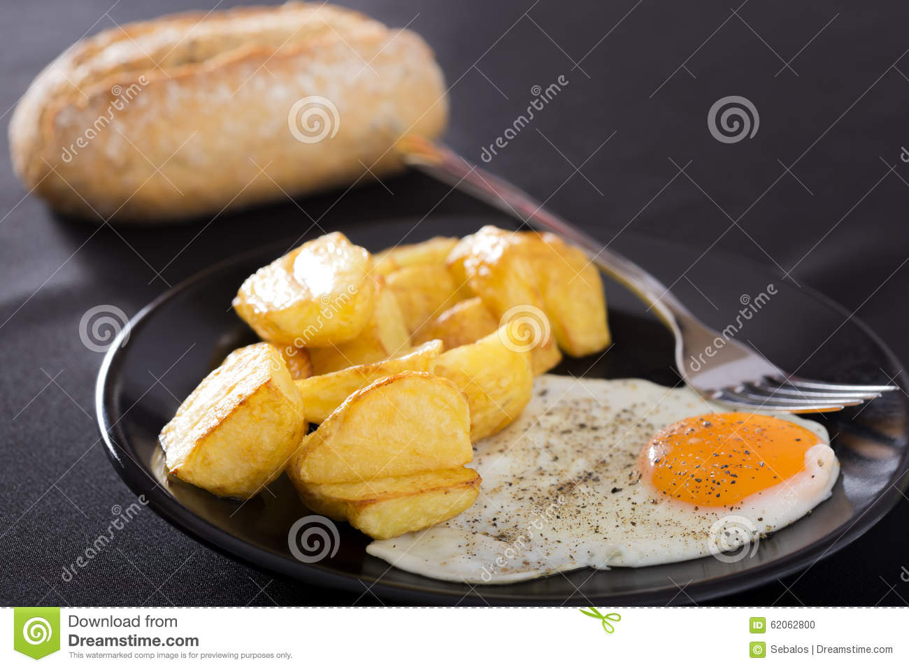 Breakfast with fried potato and eggs on a dark plate.