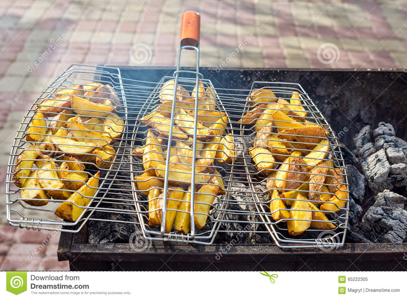 Fried potatoes on grill. Outdoors barbecue weekend.
