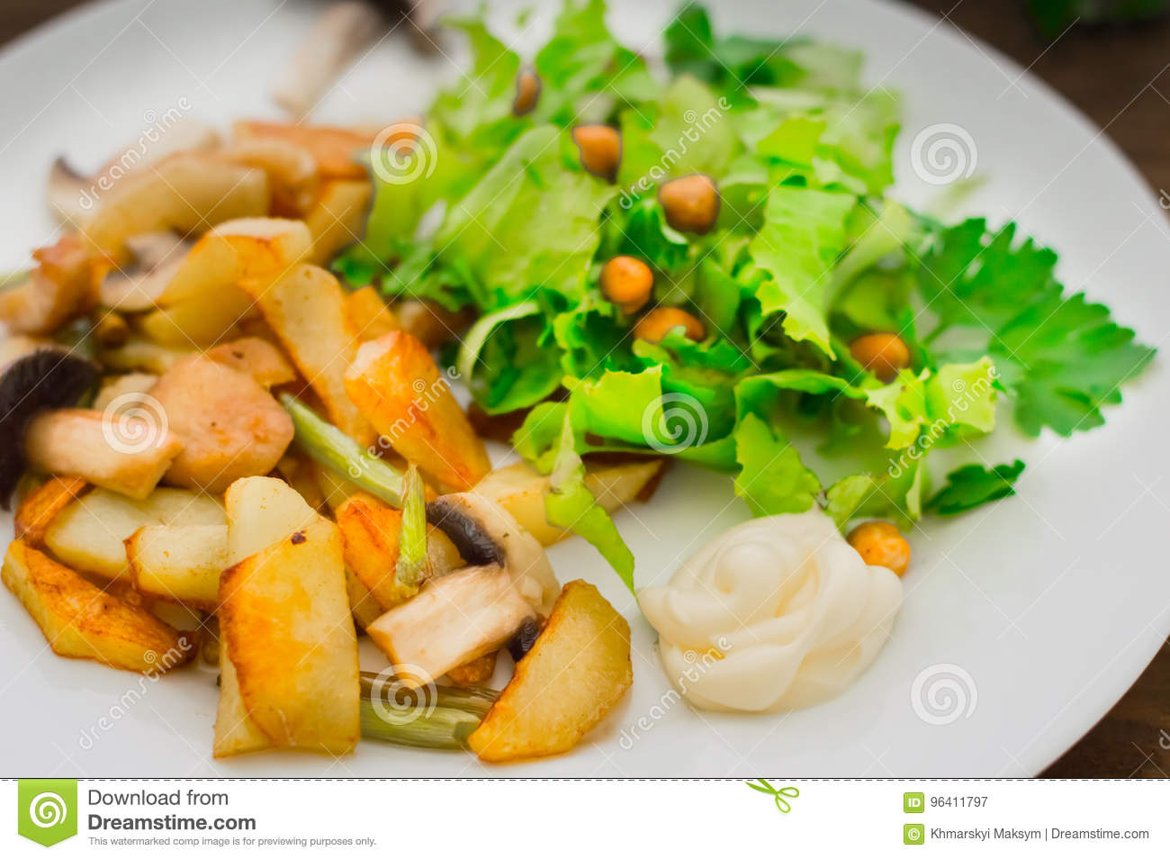 Fried potatoes roasted with wild mushrooms on white plate and green lettuce on wooden table background. Wooden background. Top vie