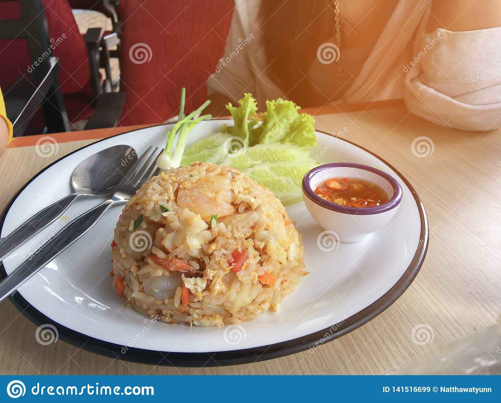 Fried rice with shrimp in Thai decorate the dish with green onion, cucumber, lettuce, chilli and lemon
