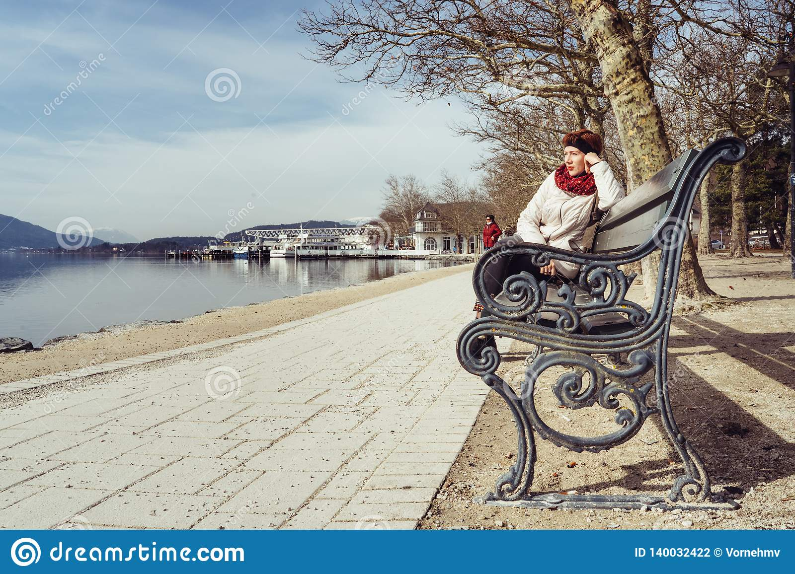Friedelstrand, Südufer Wörthersee, Klagenfurt, Kärnten, Österreich - 20. Februar 2019: Eine Frau, die auf einer Parkbank auf sit