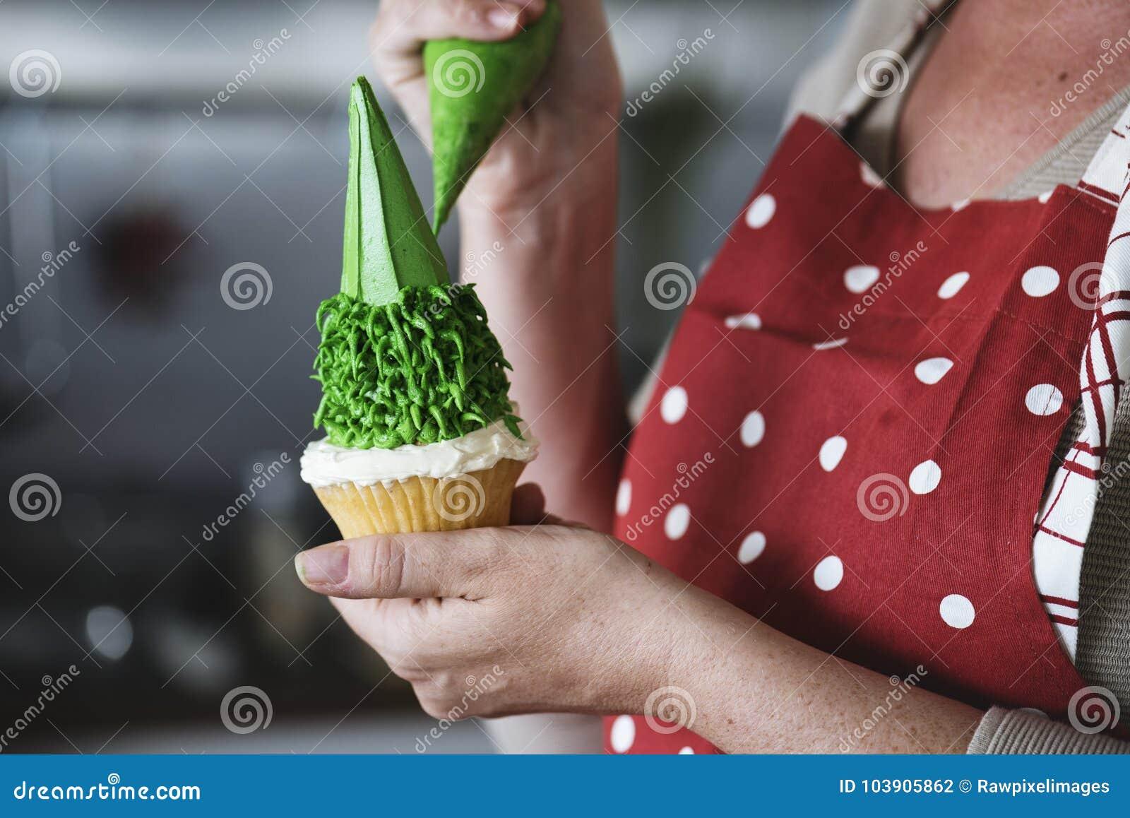 Friedliche Zuckerglasur des Bäckers auf einen kleinen Kuchen