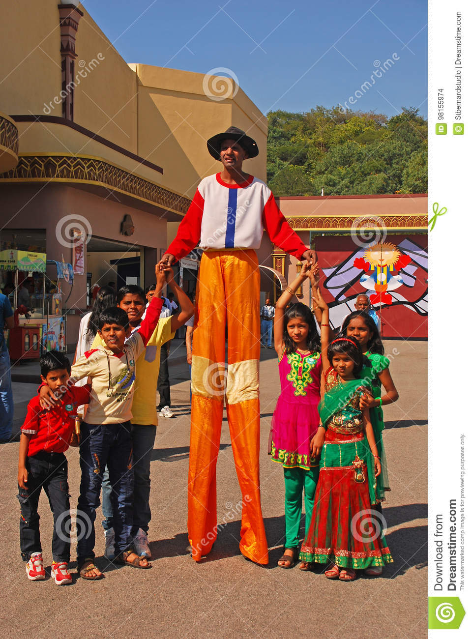 Friendly Clown on Stilts smiling widely while posing with Children at Ramoji Film City - world`s largest film studio complex