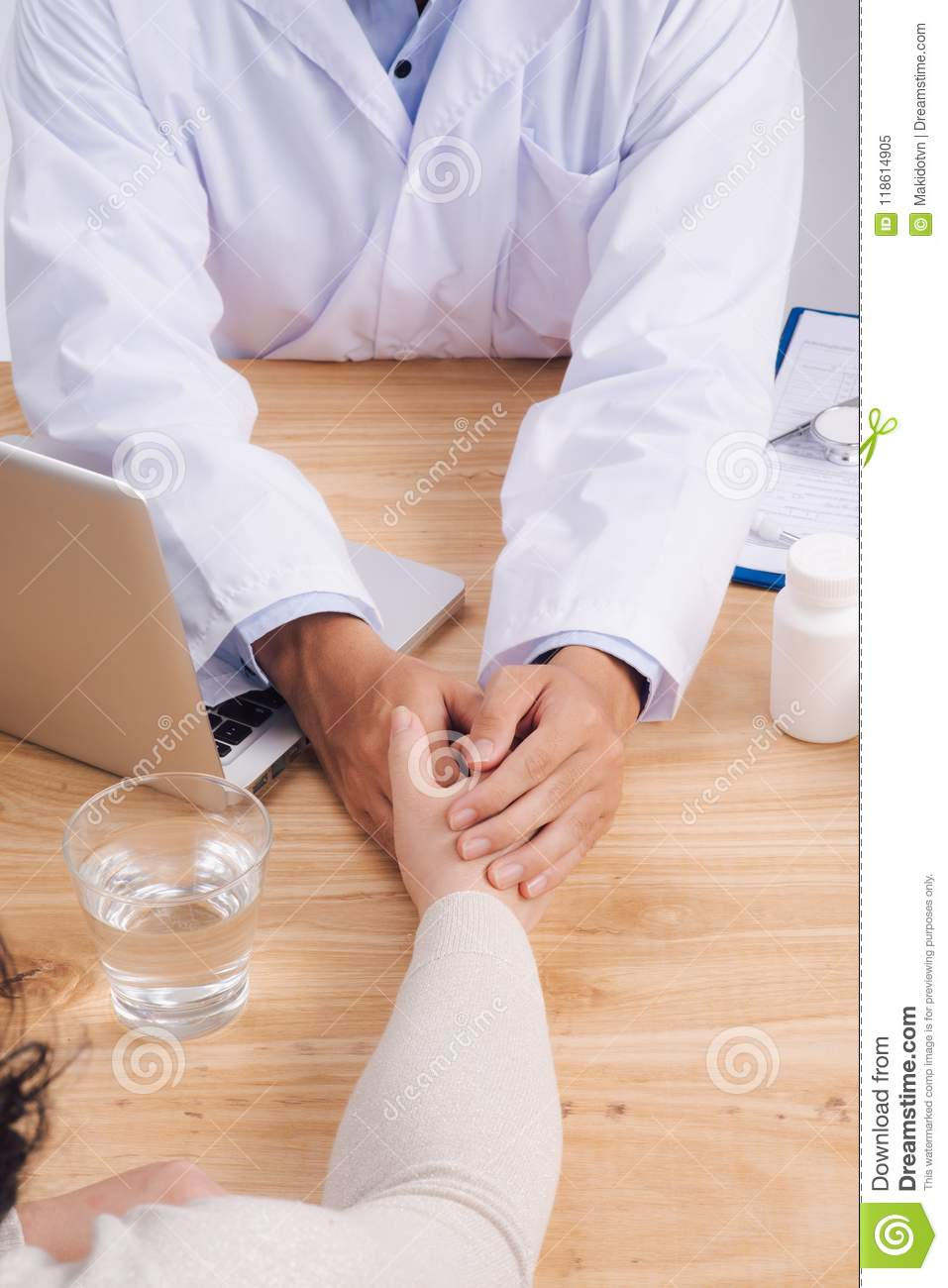 Friendly doctor hands holding patient hand sitting at the desk f