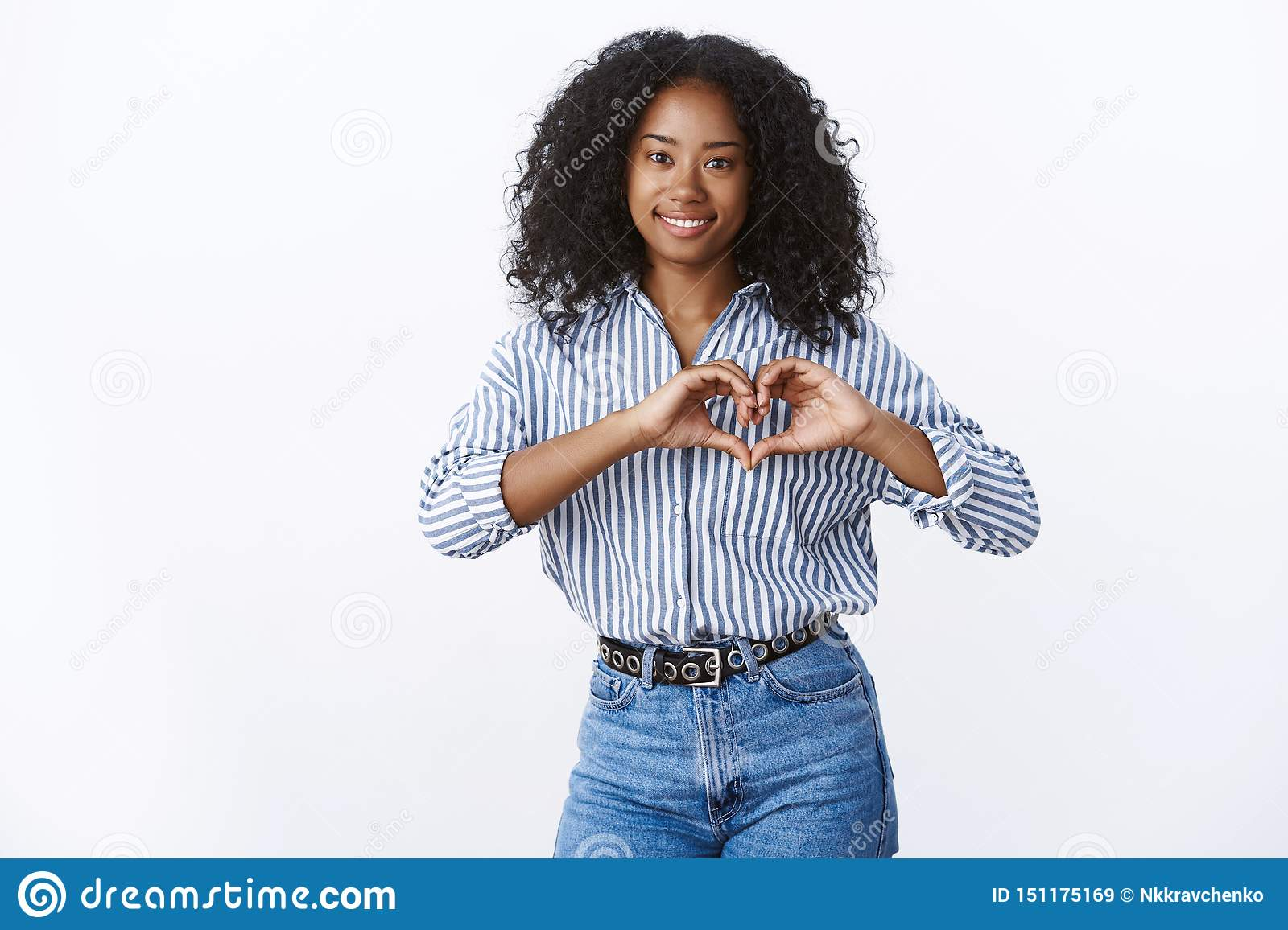 Friendly-looking charming happy young dark-skinned female showing heart gesture romantic love sign smiling broadly