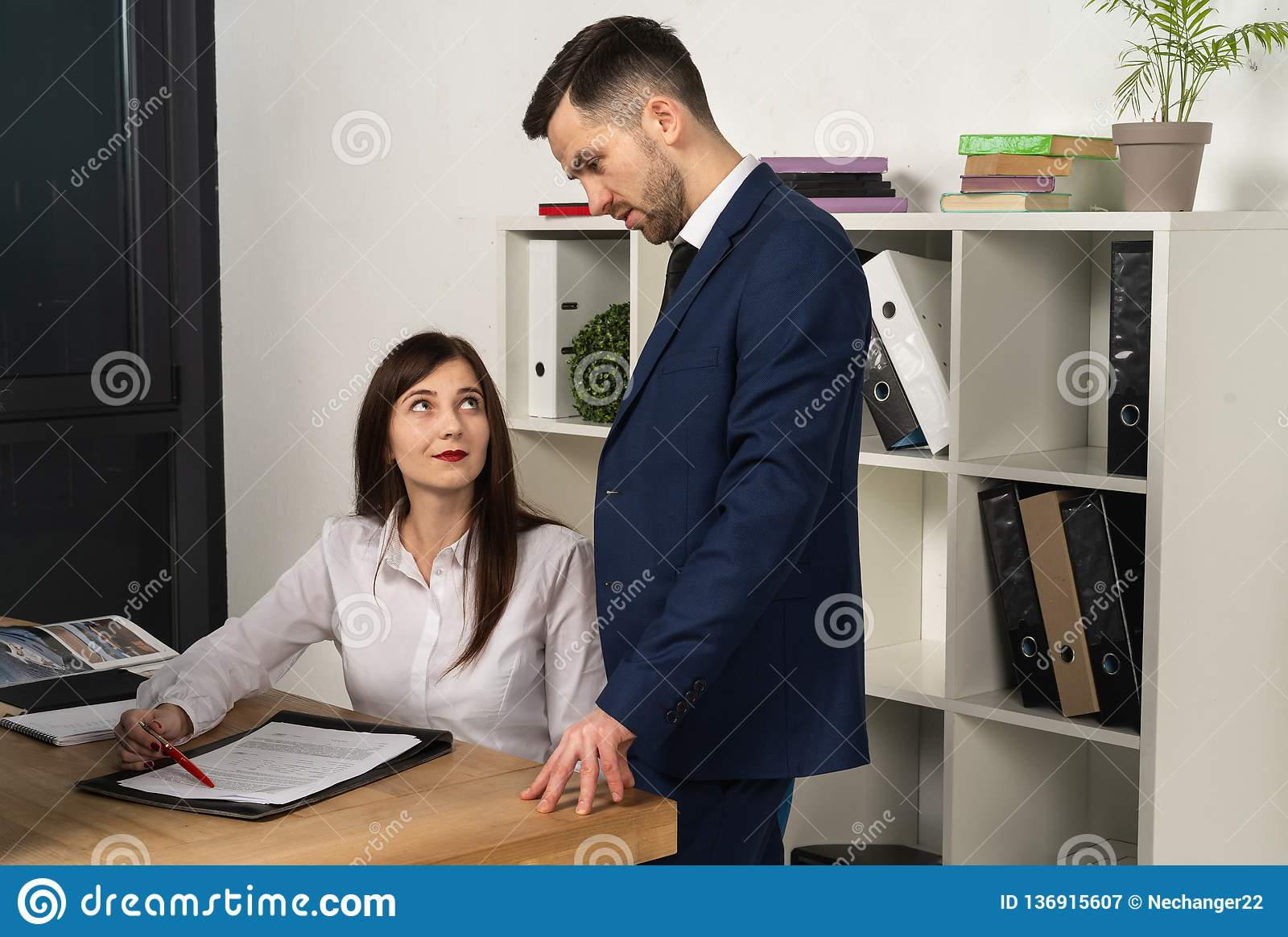 Friendly mentor explaining task for young employee