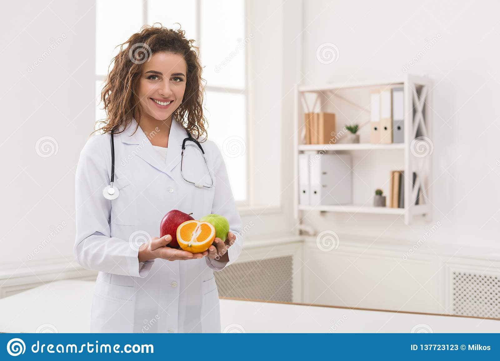 Friendly nutritionist holding fresh fruit, copy space