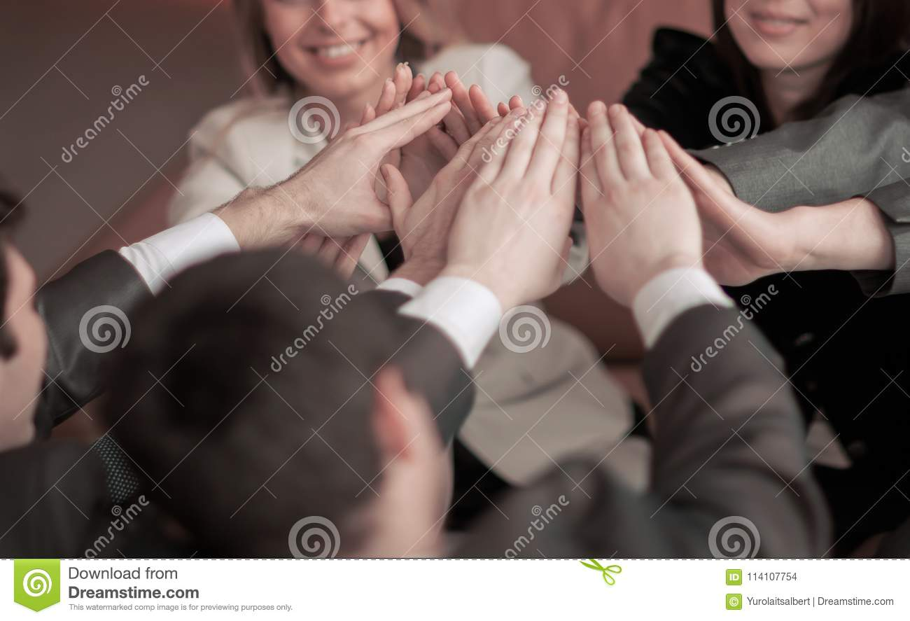 Friendly professional business team, pleased with his victory, hands clasped together