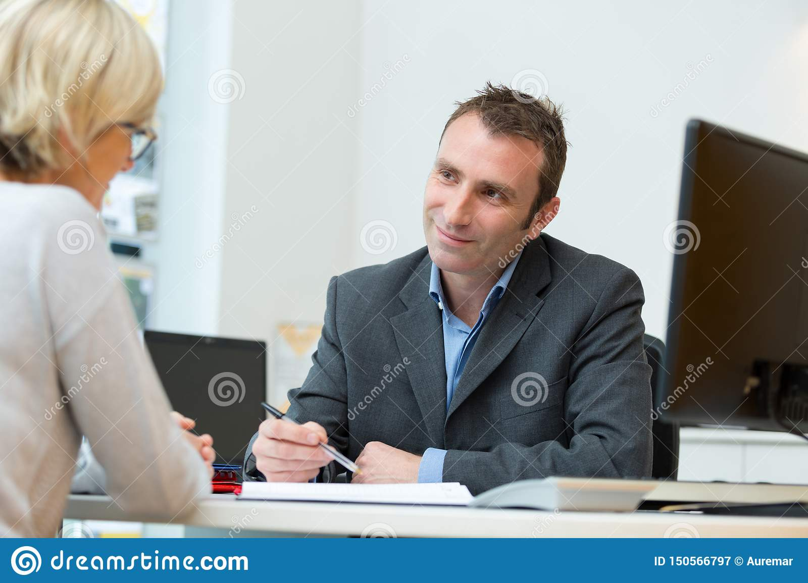 Friendly smiling businessman and businesswoman in office