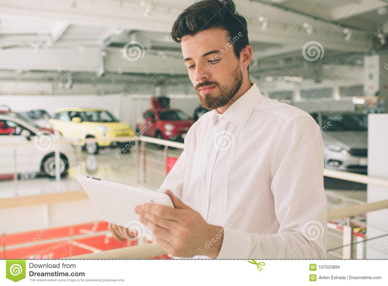 Friendly vehicle salesman presenting new cars at showroom. Photo of young male consultant showing new car in auto show