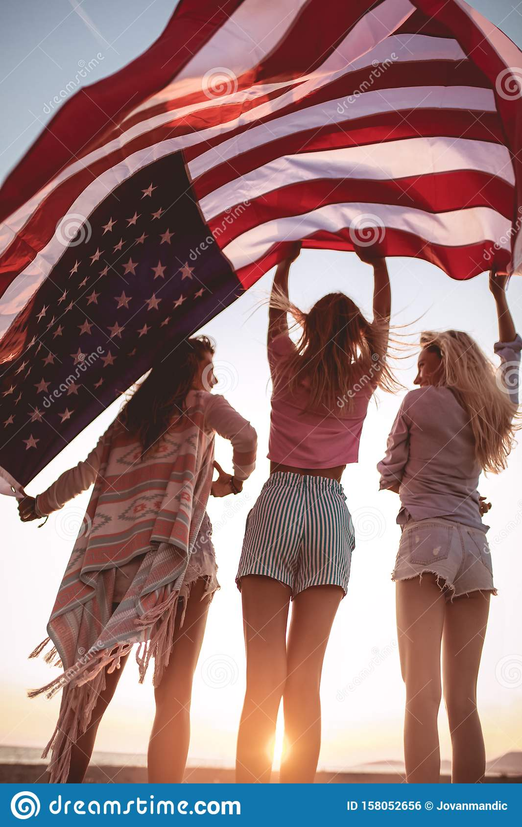 Friends carrying american flag on the beach