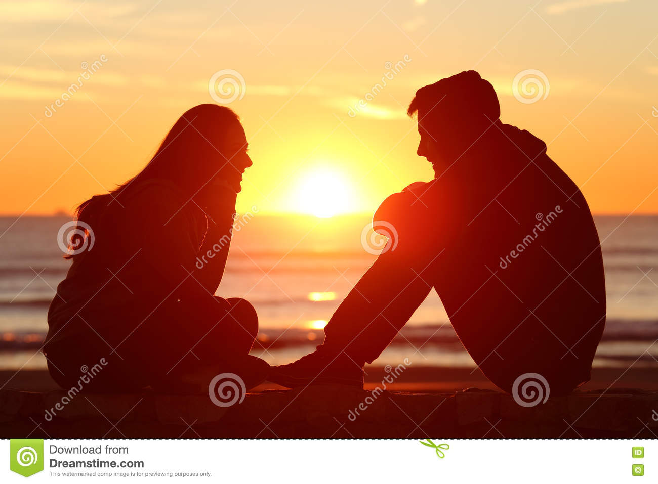 Friends or couple of teens facing at sunset