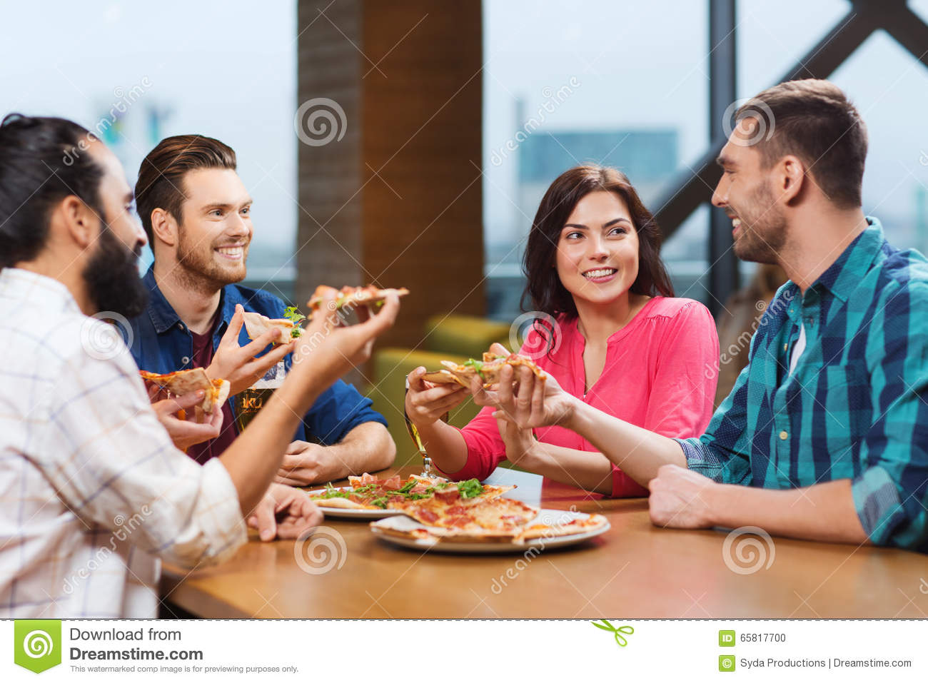 ... smiling friends eating pizza and drinking beer at restaurant or pub