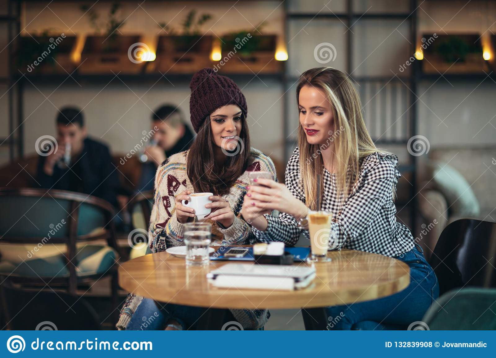 Friends enjoying coffee together in a coffee shop and using phone