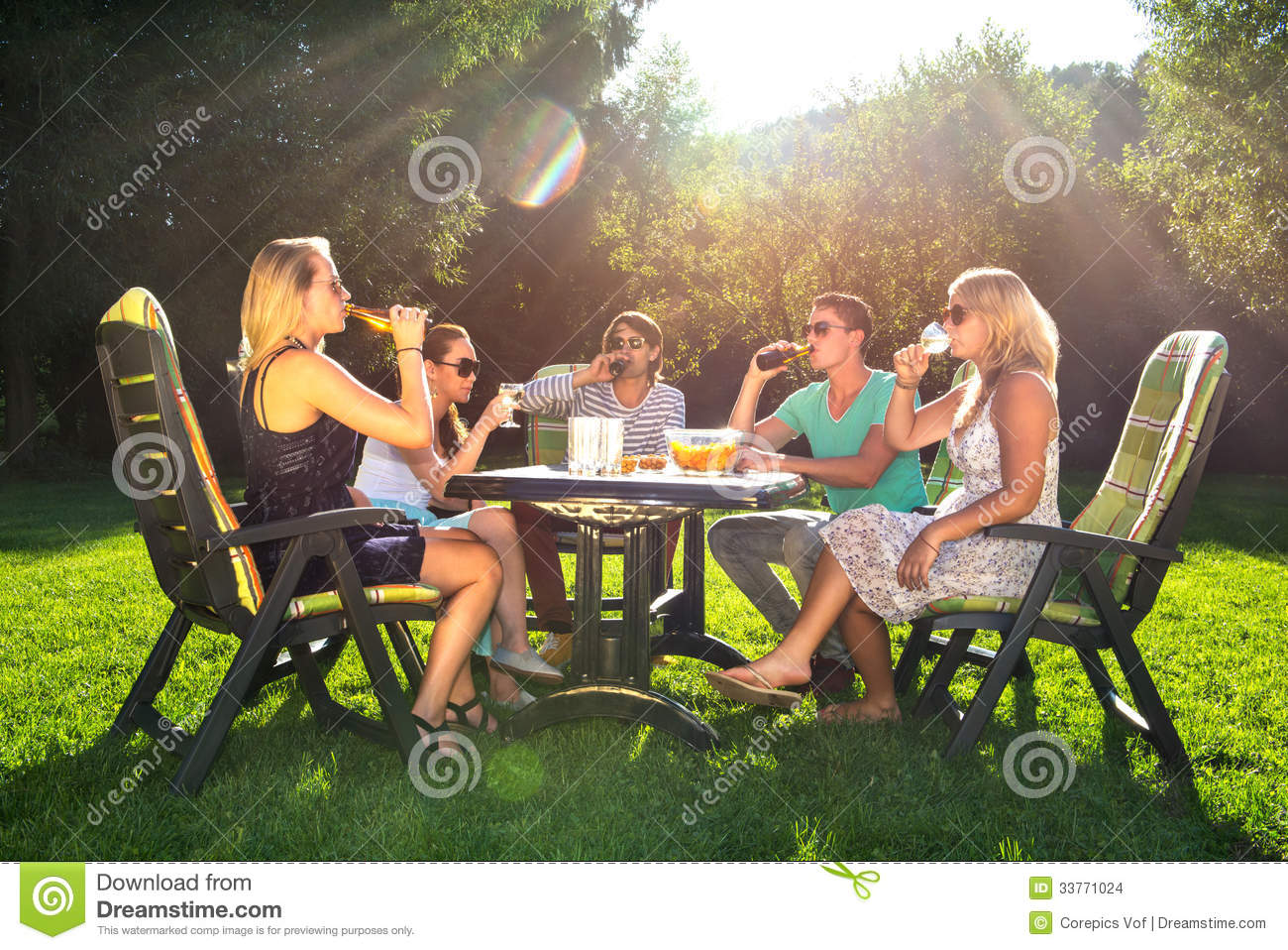 Group of young friends enjoying a garden party on a sunny afternoon.