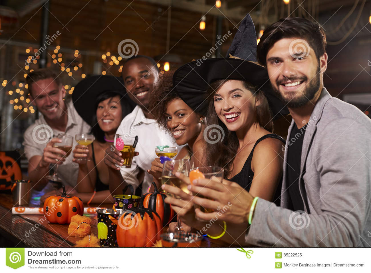 Friends enjoying a Halloween party at a bar look to camera