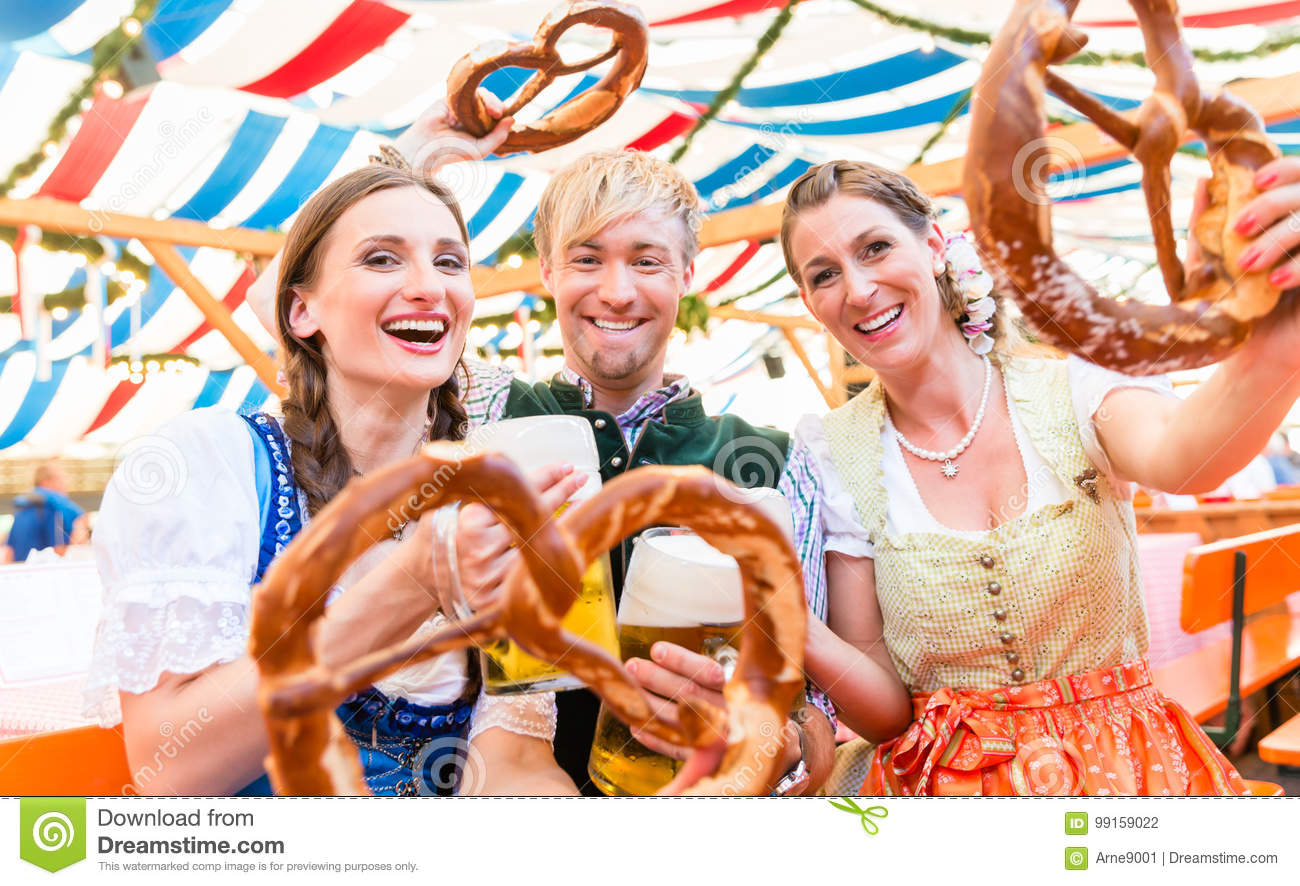 Friends with giant pretzels in Bavarian beer tent