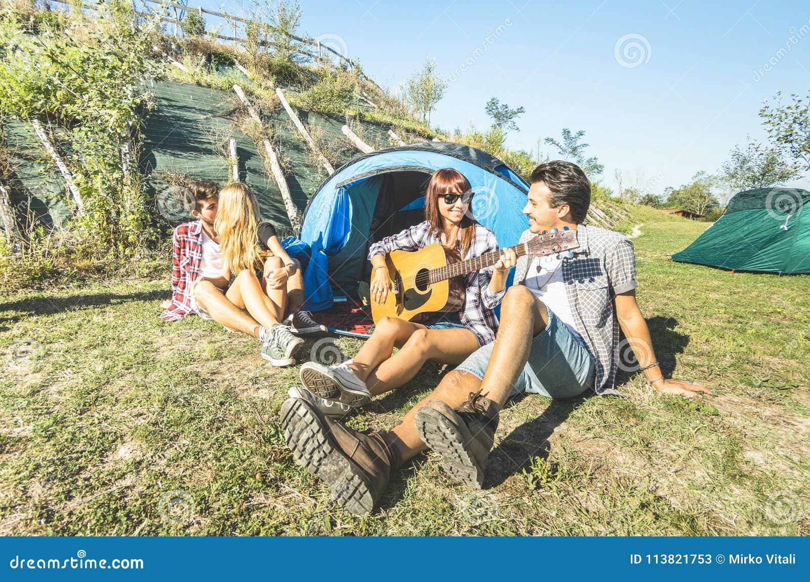 Friends group having fun outdoor cheering at picnic camp