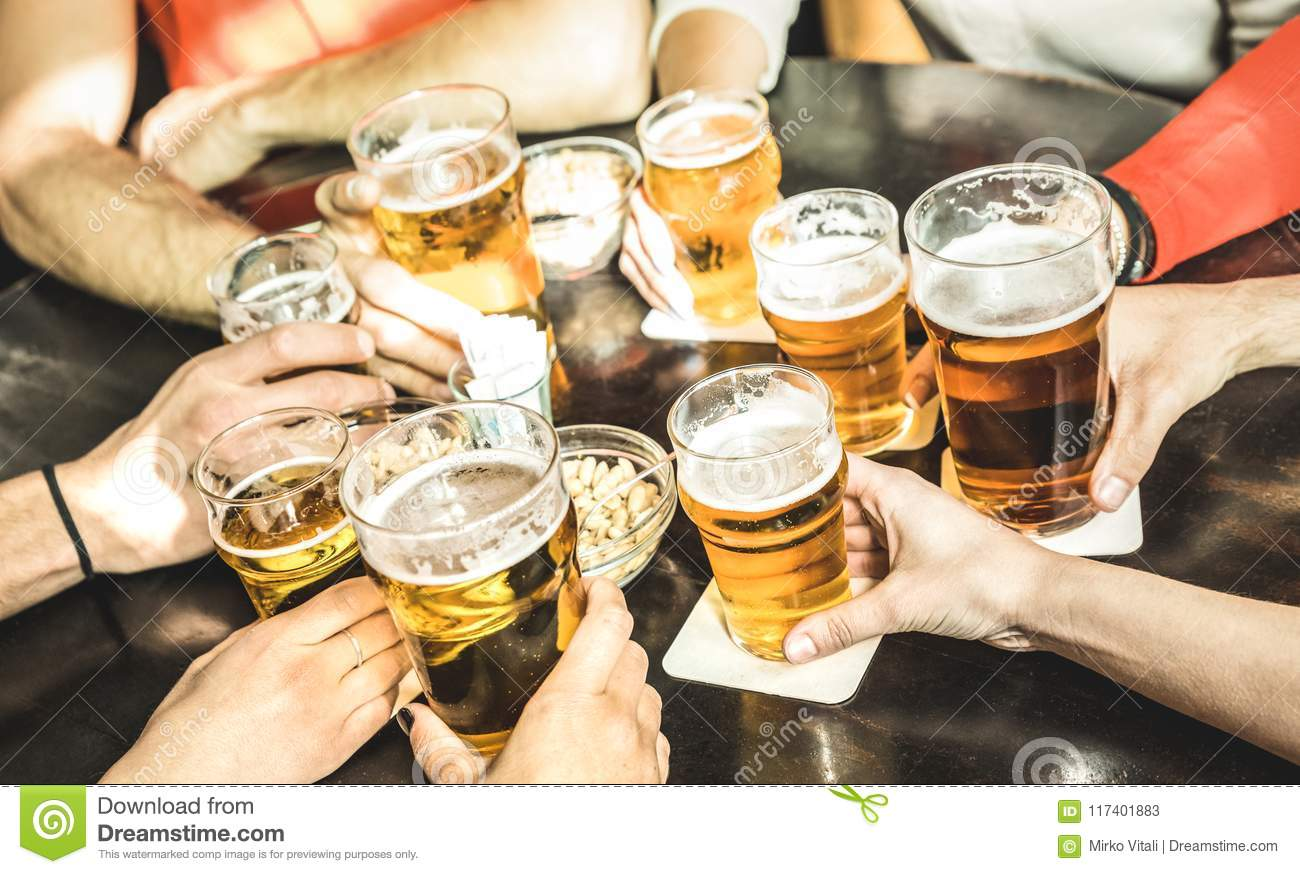 Friends hands drinking beer at brewery pub restaurant - Friendship concept with young people enjoying time together and having ge