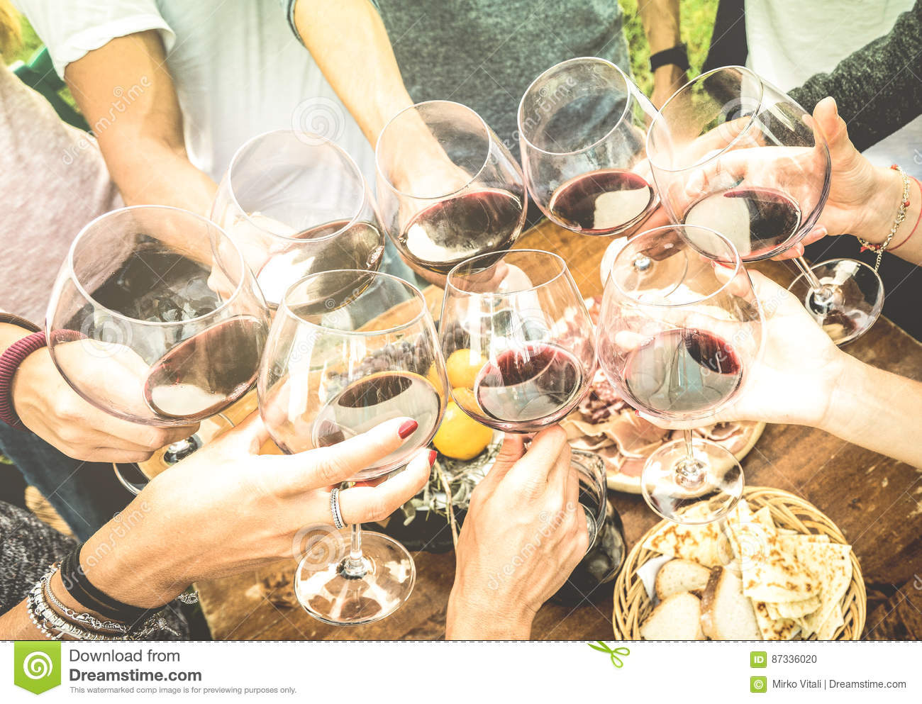 Friends hands toasting red wine glass and having fun outdoors