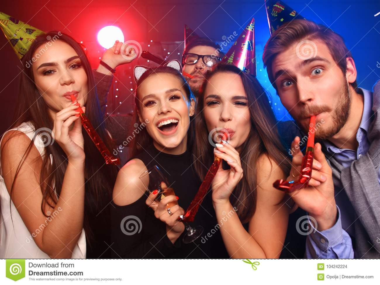 Friends making big party in the night. Five people throwing confetti and drinking champagne.