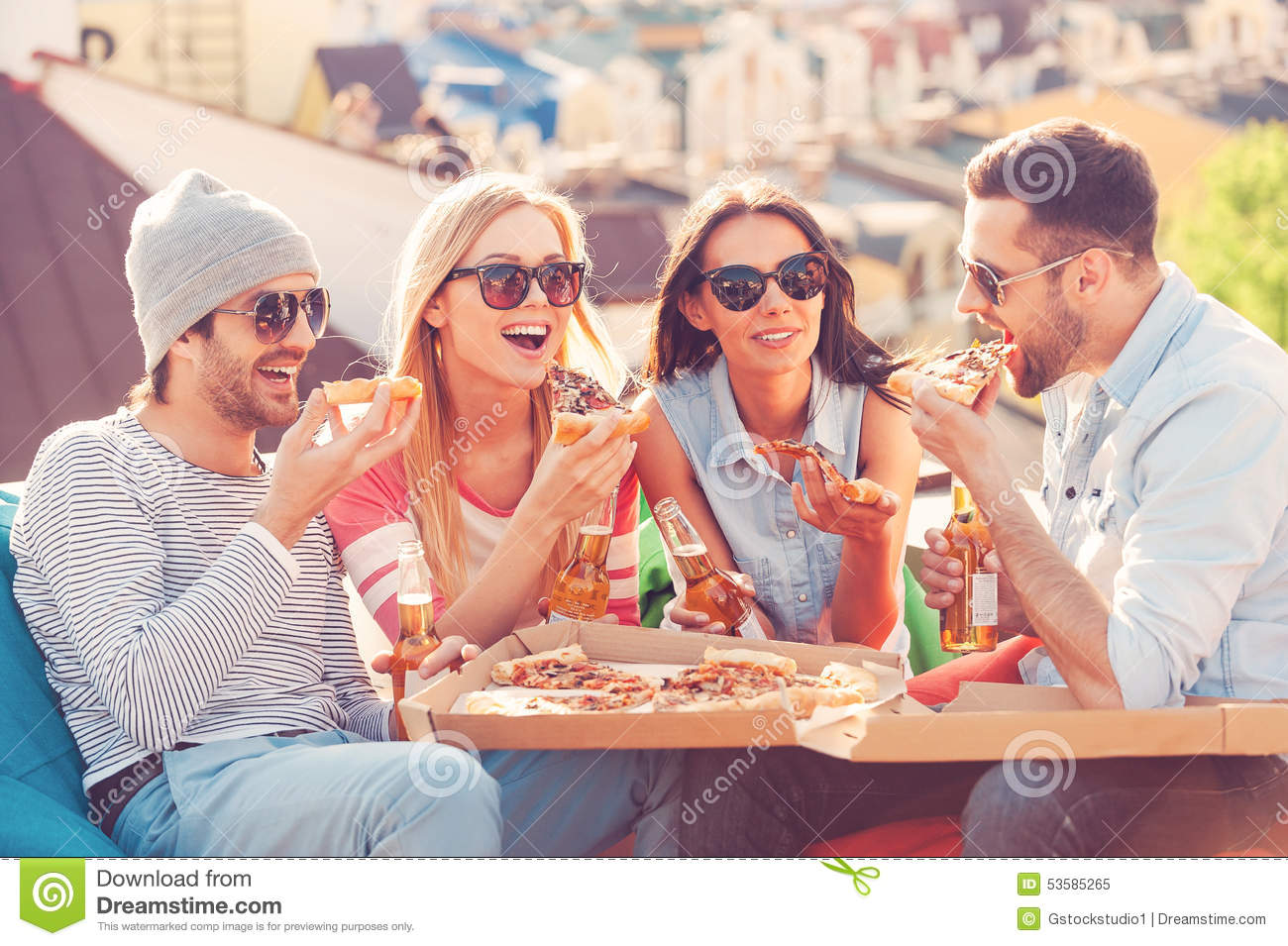 Four young cheerful people eating pizza and drinking beer while ...