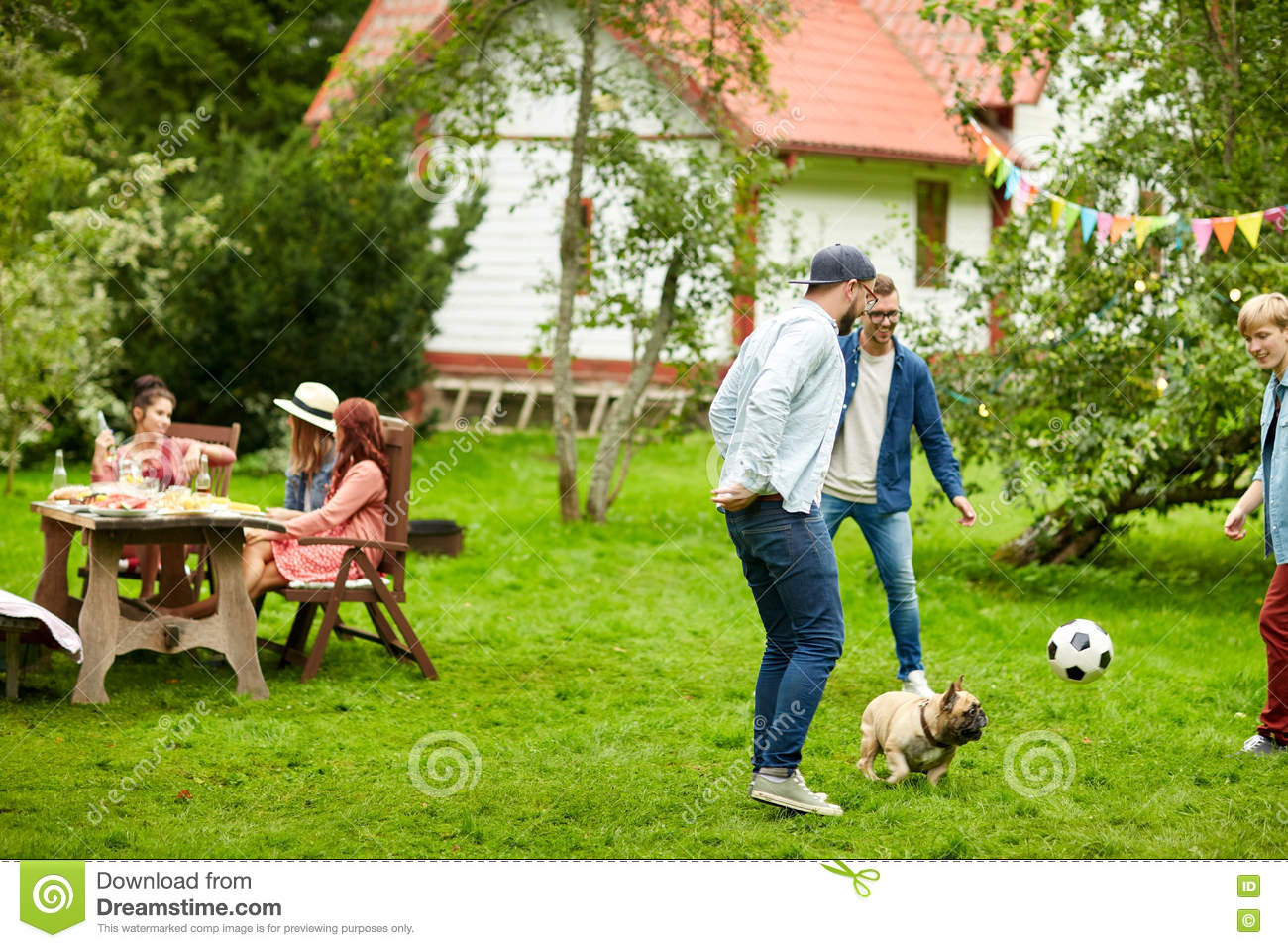 Friends Playing Football With Dog At Summer Garden Stock