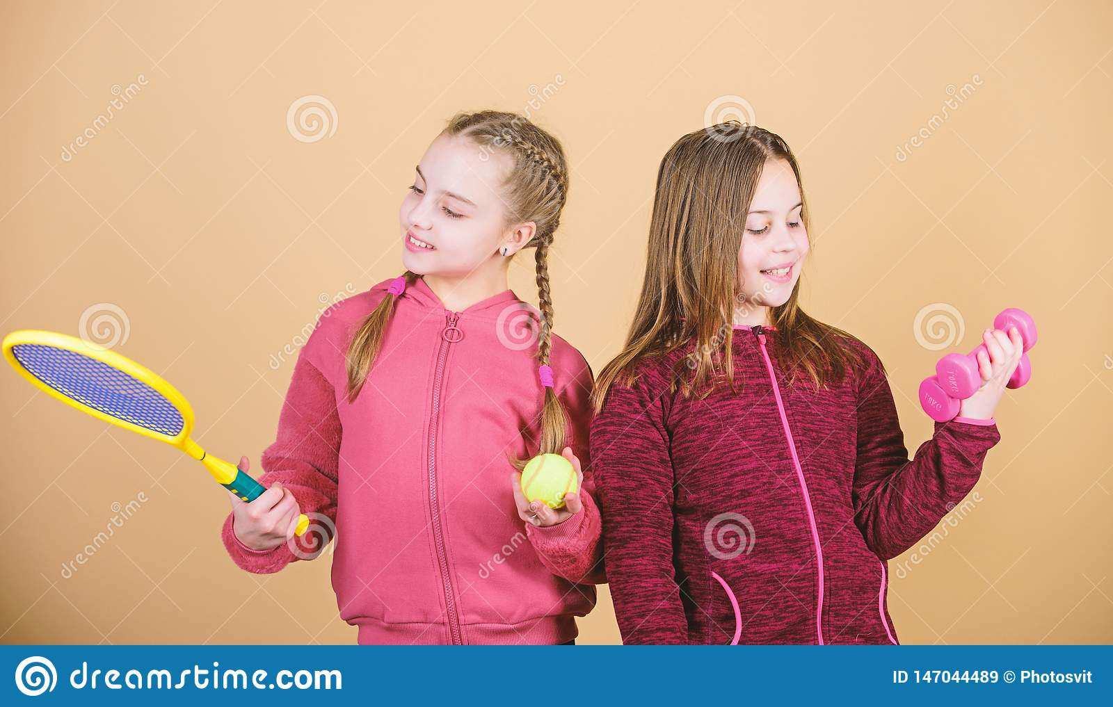 Friends ready for training. Ways to help kids find sport they enjoy. Girls cute kids with sport equipment dumbbells and
