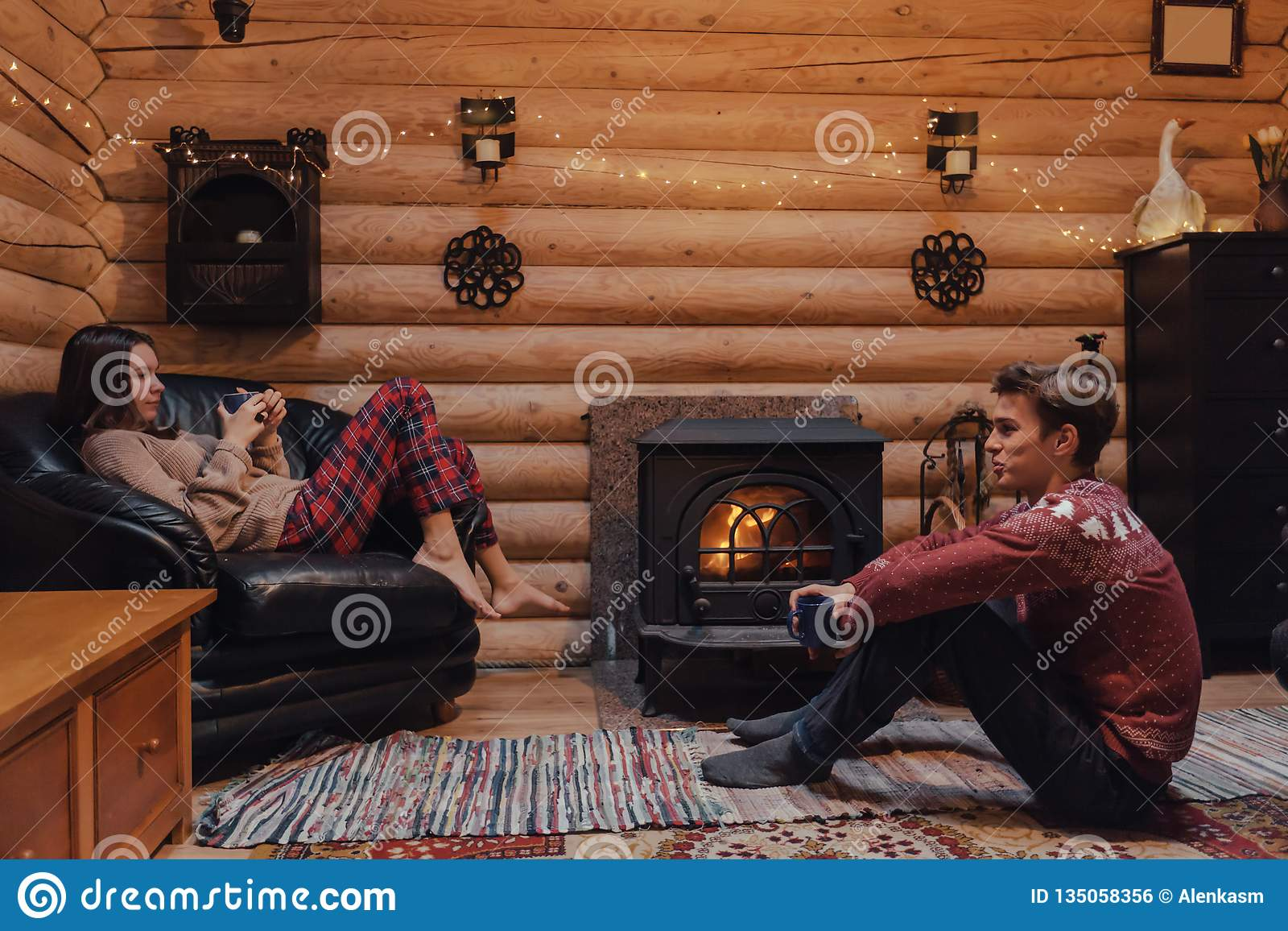 Friends Relaxing By The Fireplace In Log Cabin Stock Photo