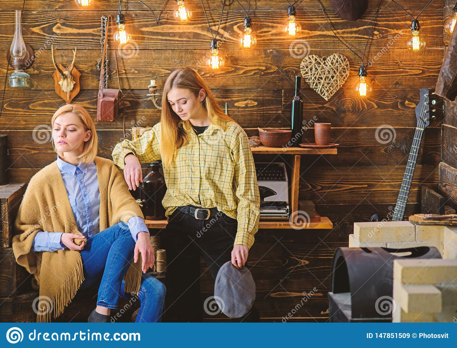 Friends or sisters spend pleasant evening in gamekeepers house, interior background. Vacation in woods concept. Girls on
