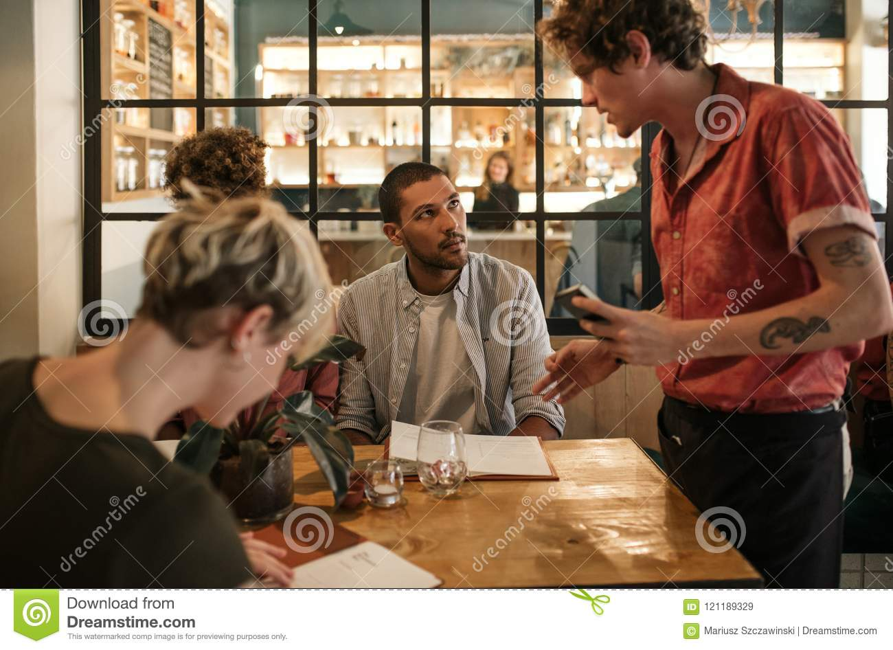 Friends Sitting In A Restaurant Ordering Food From A Waiter
