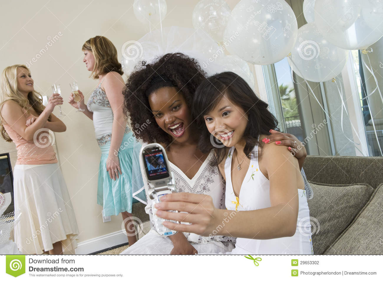Happy female friends taking self portrait through cell phone with ...