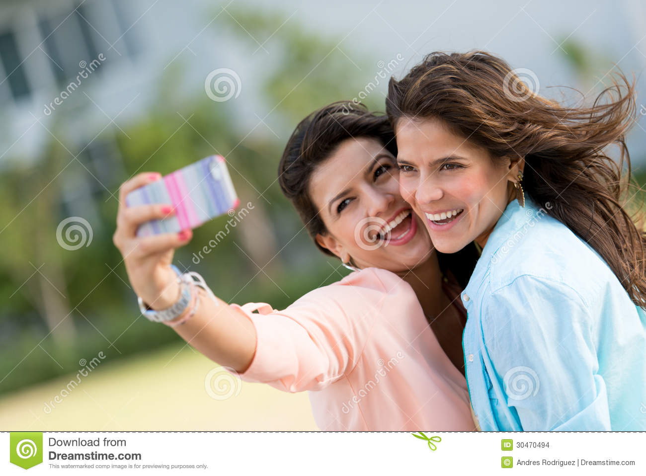 Happy friends taking a self portrait with a cell phone.