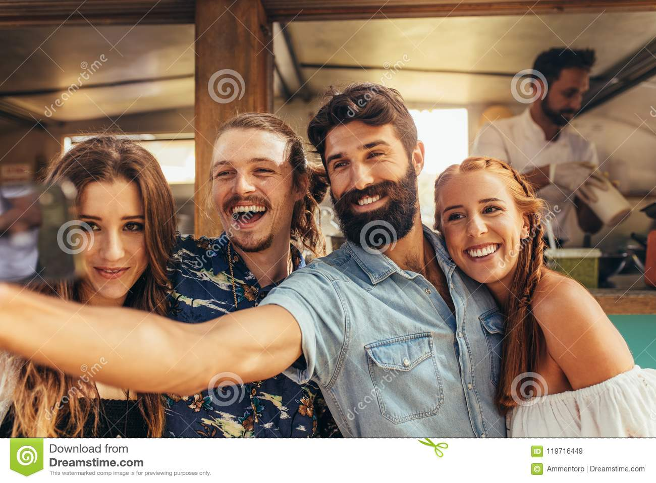 33178a6dfe1a5 Handsome young men taking selfie with friends. Group of men and women  making selfie at summer festival.