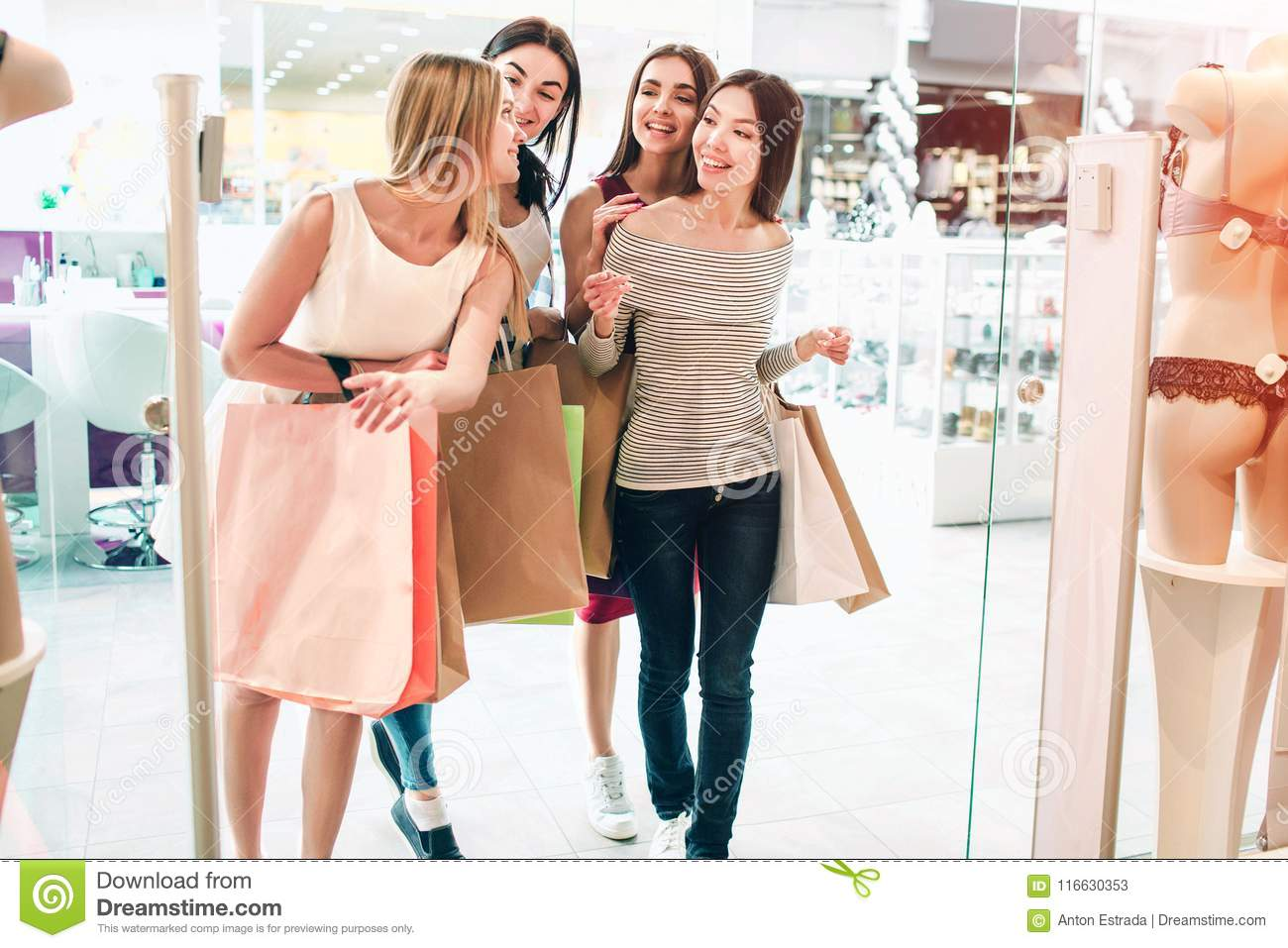 Friends are talking among themselves and walking into lingerie store. They are holding bag. Girls are shopping and