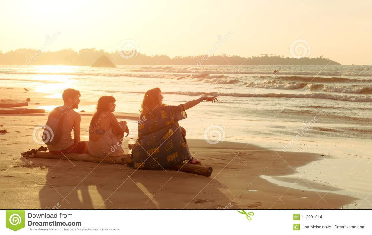Friends two young women and man sit on tropical seaside beach at sunset and look at water. Summer trip, vacation.