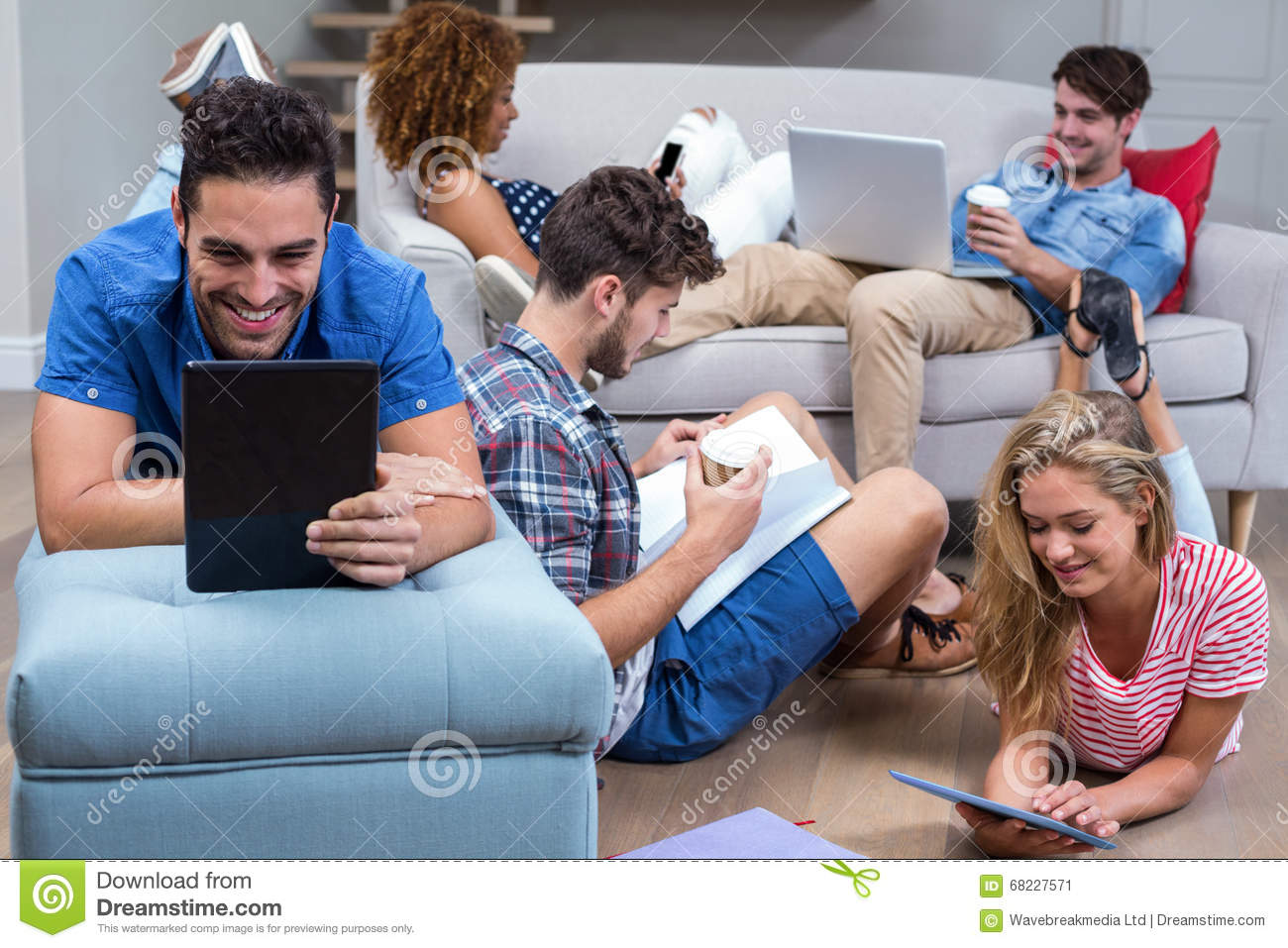 Friends using modern technologies in living room stock for Young modern living room