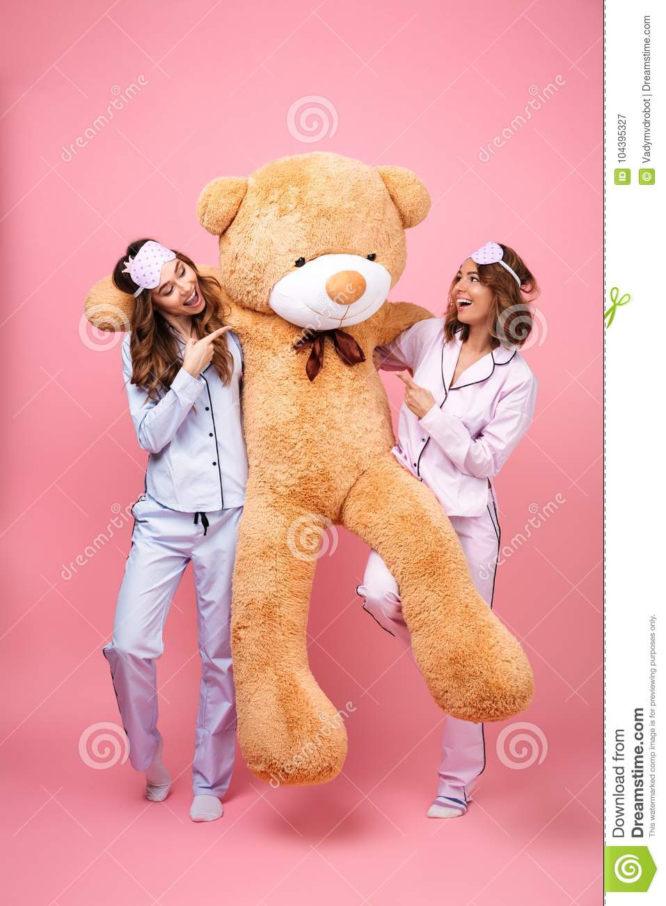 Photo of two amazing friends women in pajamas isolated over pink background  hug big teddy toy bear. Looking ae pointing. e0f515e02