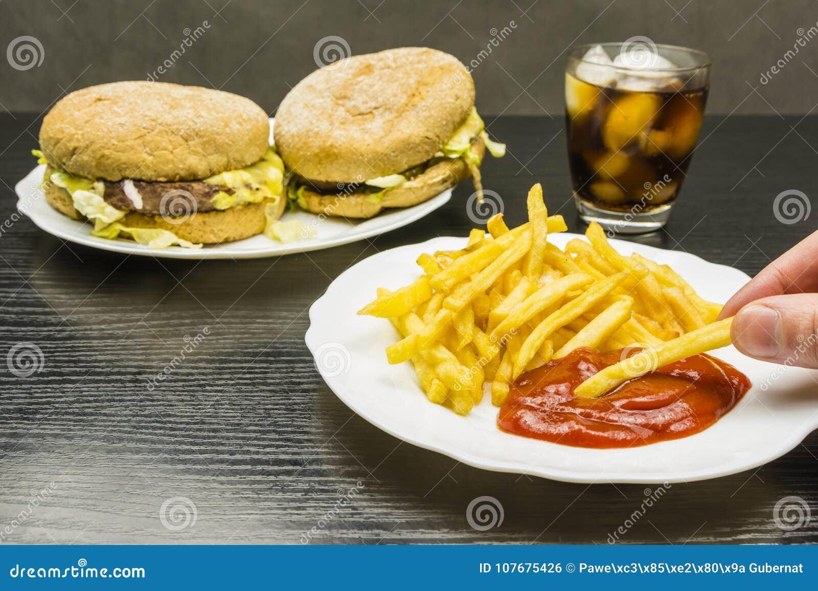Frieten en ketchup op een plaat en een hamburger en kola met I