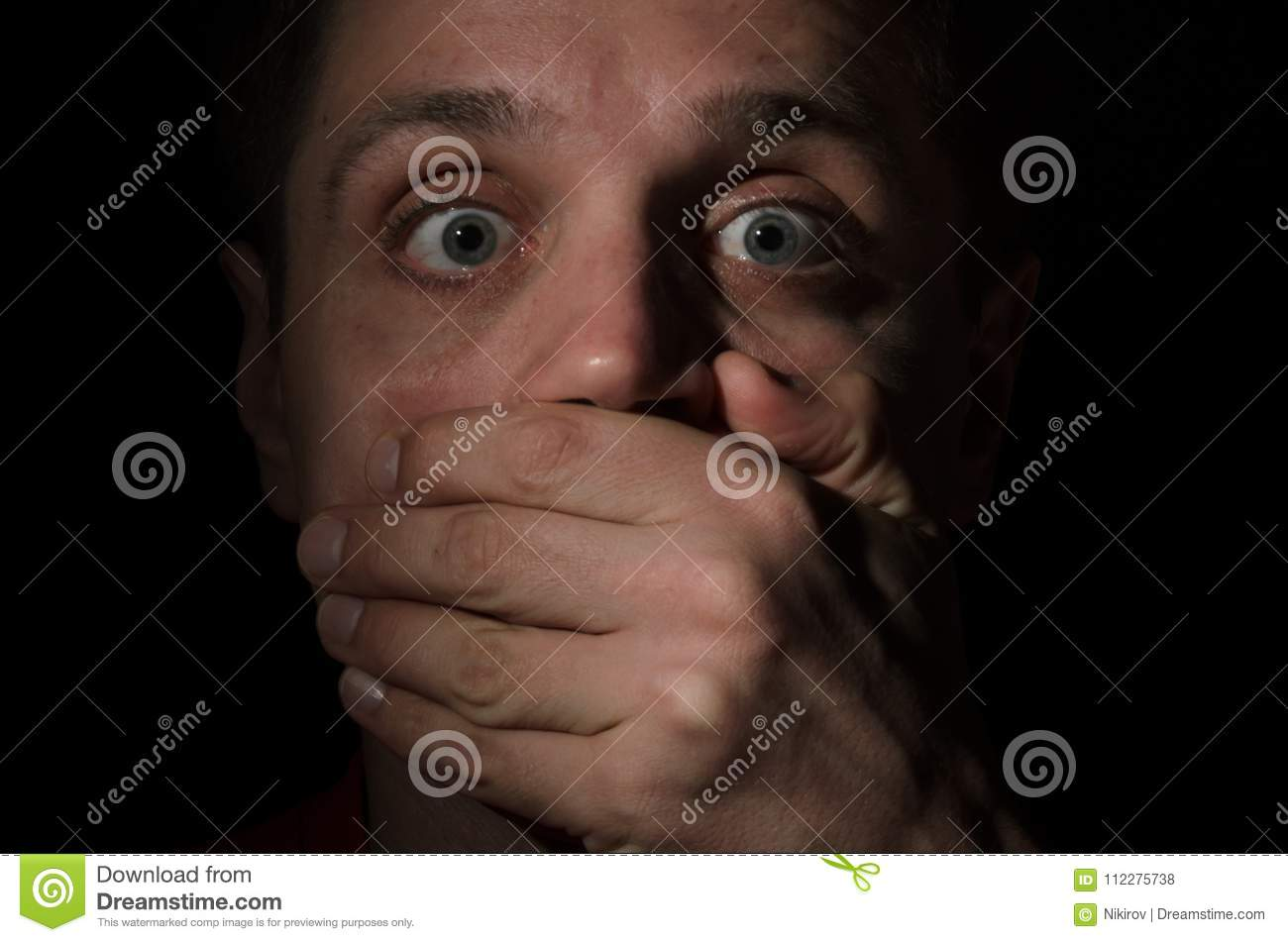 A frightened face of a man with eyes full of horror, who was forcibly covered his mouth with his hand isolated on black background